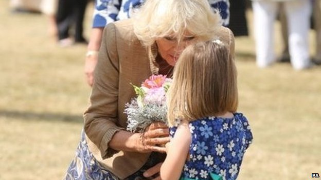 Five year old Hollie Ford present the Duchess of Cornwall with a posy on her arrival at the Sandringham flower show held on the Royal Estate in Norfolk.