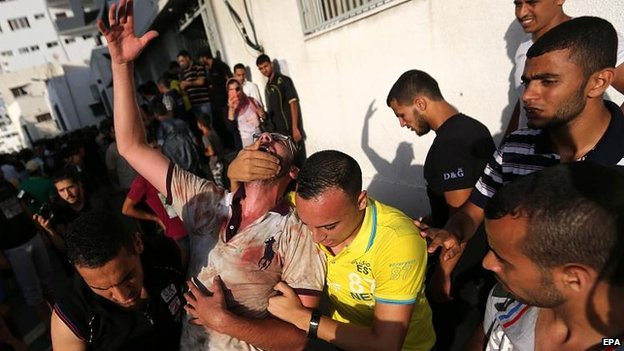 Palestinians react after the deaths at the market near Gaza City, 30 July
