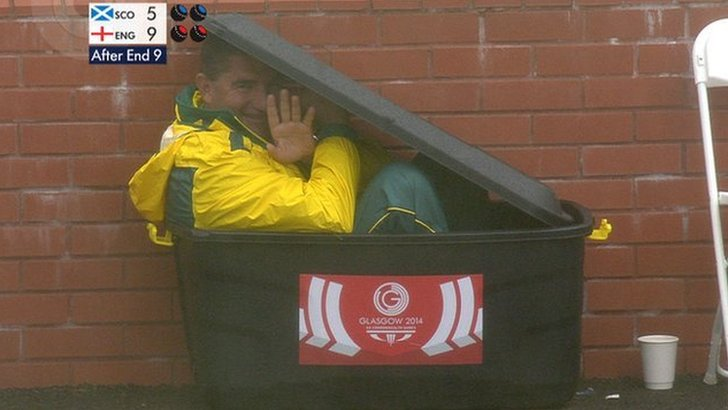 Australian bowls player Kelvin Kerkow uses a box to shelter from the rain during a match between Scotland and England.