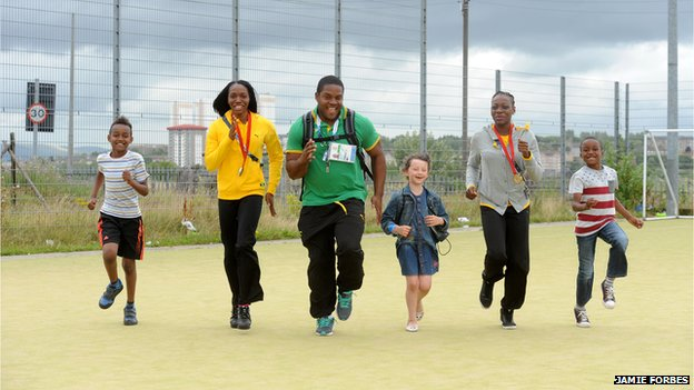 Novlene Williams-Mills (second left), O'Dayne Richards (centre) and  Kimberly Williams (second right) with some of the schoolchildren they met in north Glasgow