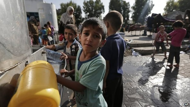 Displaced Palestinian children collect water at the Abu Hussein UN school, in Jabaliya refugee camp, northern Gaza Strip, 30 July 2014