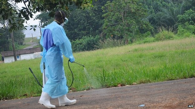 Aid worker spraying disinfectant outside a hospital in Liberia