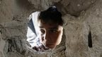 A boy looks through a hole on the wall made by the shelling at the Abu Hussein U.N. school in the Jebaliya refugee camp in the northern Gaza Strip, 30 July 2014
