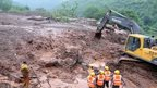 "Excavators digging through mud and debris at the scene of a landslide in Malin village in Pune district, India""s western state of Maharashtra, on July 30, 2014."