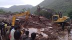 Excavators digging through mud and debris at the scene of a landslide in Malin village in Pune district, India's western state of Maharashtra, on July 30, 2014.