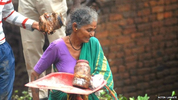 A villager retrieving her belongings at the site of the landslide in India's Malin village on 30 July, 2014