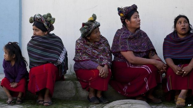 Women gather before taking part in the burial of 31 villagers massacred during the civil war in 1982 in Santa Maria Nebaj, Guatemala, 30 July 2014