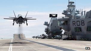 A F-35B Lightning II jet landing vertically on aircraft carrier HMS Queen Elizabeth.