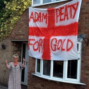 Audrey Stephenson stood near a 'Adam Peaty for gold' banner
