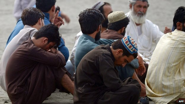 Relatives wait for news of their missing loved ones who are feared drowned in Clifton beach in Karachi on 31 July 2014.