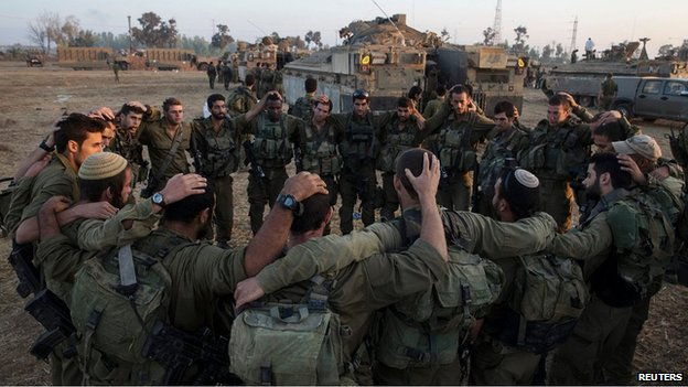 Israeli troops in a circle before entering Gaza, 30 July 2014