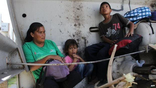 A Central American immigrant and her children sit inside La Bestia in Arriaga on 16 July, 2014.