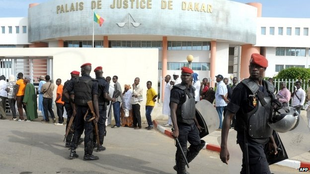 Police officers stand guard near people waiting in line in front of the Palais de Justice in Dakar, Senegal, to attend the trial of Karim Wade on 31 July 2014
