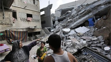 A Palestinian woman points to the wreckage of her house in Gaza City, 31 July 2014