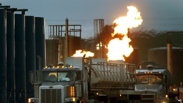 Tanker trucks, capable of hauling water and fracking liquid line up near a natural gas burn off flame and storage tanks.