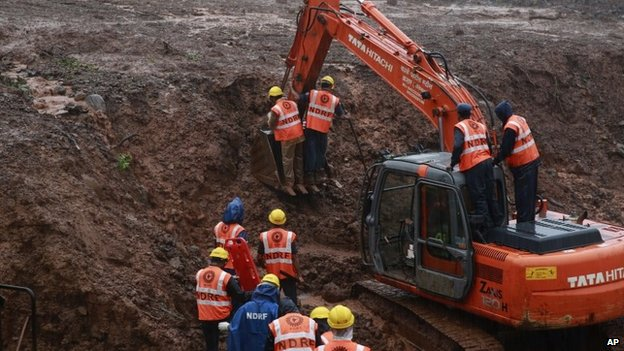 Rescuers work at the site of a massive landslide in Malin village in Pune district of western Maharashtra state, India, Thursday, July 31, 2014.