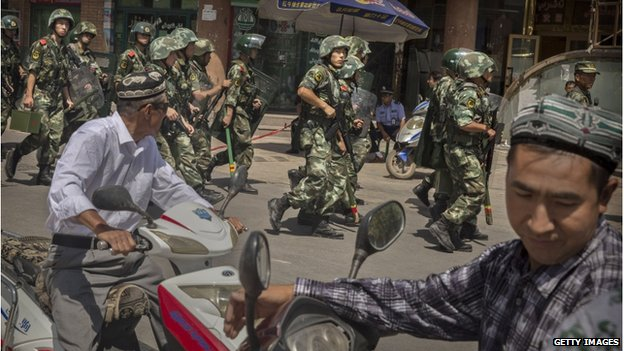 Chinese soldiers march past near the Id Kah Mosque, China's largest, on 31 July 2014 in Kashgar, China