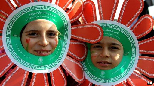Iranian children wearing paper flowers