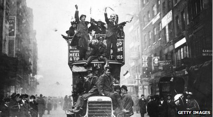 People waving flags from a London bus to celebrate the end of the war