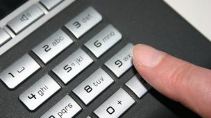 A person about to dial 9 on a telephone