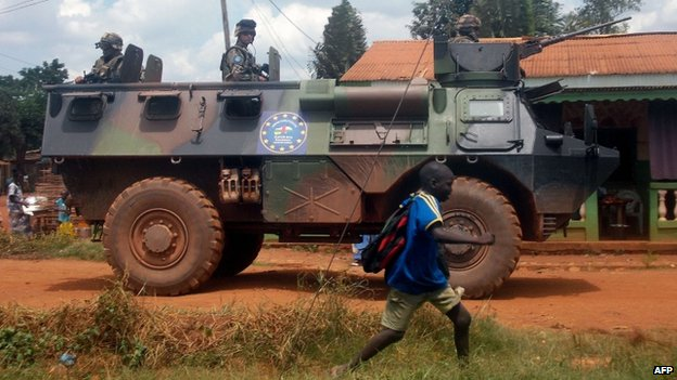 Sangaris troops patrol in an armoured personnel carrier as a schoolboy passes by, in Bangui, the Central African capital, on 13 July 2014