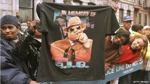 man holds up T-shirt in memory of BIG