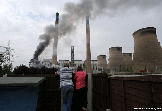 Residents look on as smoke rises from a fire at Ferrybridge C