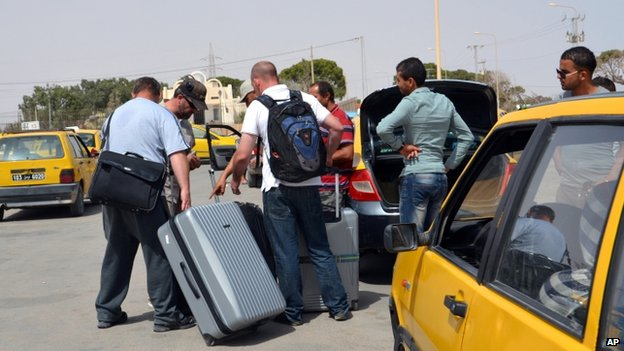 Tunisian taxi drivers wait for clients fleeing from Libya at the Ras Ajdir border post between Libya and Tunisia (31 July 2014)