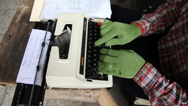 A Liberian typist at work using gloves as a protective measure to avoid the deadly Ebola virus in Monrovia (30 July 2014)