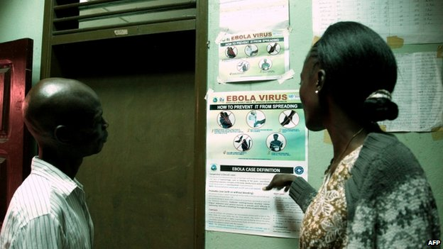 Liberian people read an information sign about Ebola set on a wall of a public health centre in Monrovia (31 July 2014)
