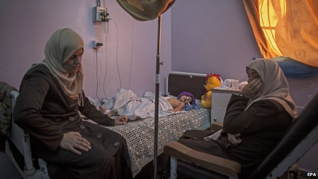 The mother and a friend of a child injured in an Israeli airstrike sit by her bed