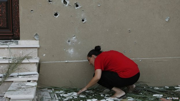 An Israeli woman surveys the damage after a rocket fired by Palestinian militants in Gaza landed in the southern town of Kiryat Gat