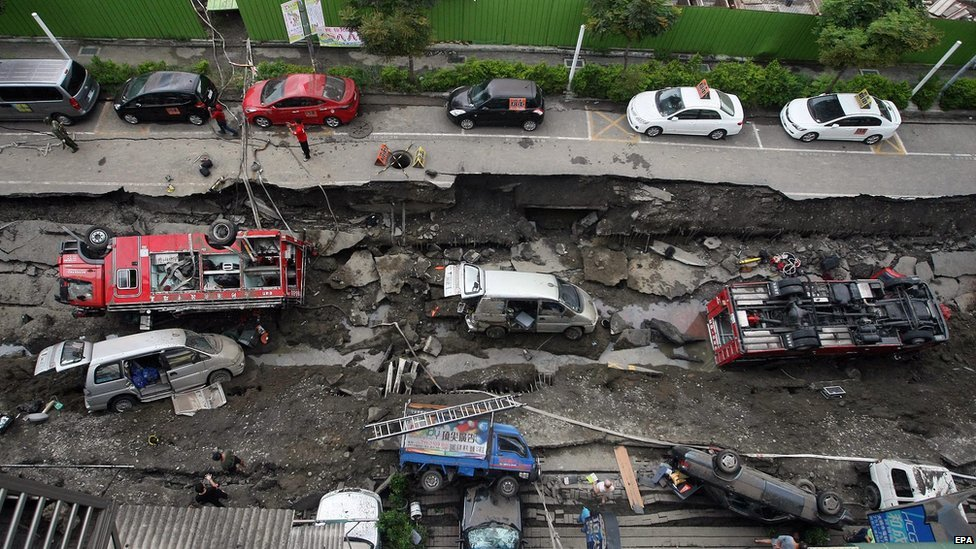 Two fire engines and other vehicles lie on their side on a caved-in road caused by underground explosions in Kaohsiung City, southern Taiwan, on 1 August 2014