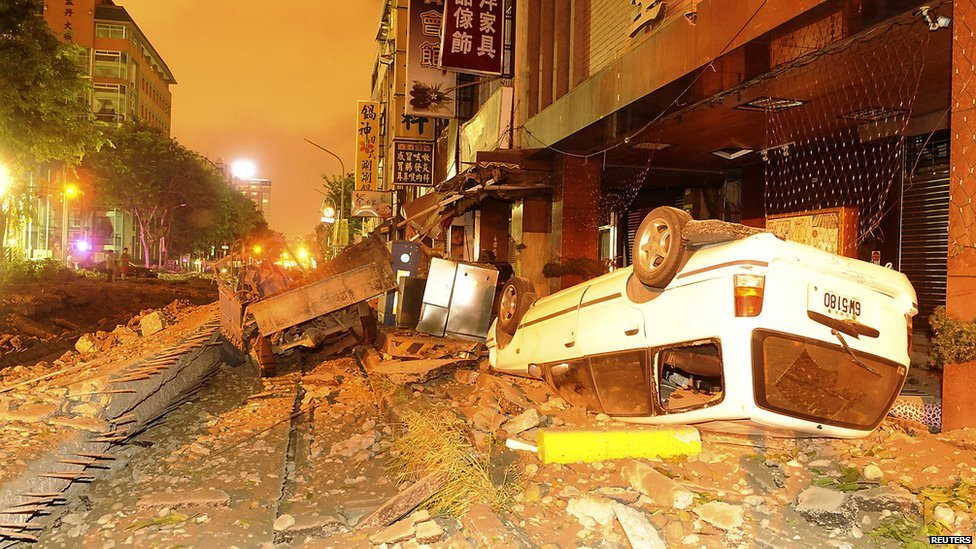 Damaged vehicles line an destroyed street as flames continue to burn from multiple explosions from an underground gas leak in Kaohsiung, Taiwan, on Friday 2014