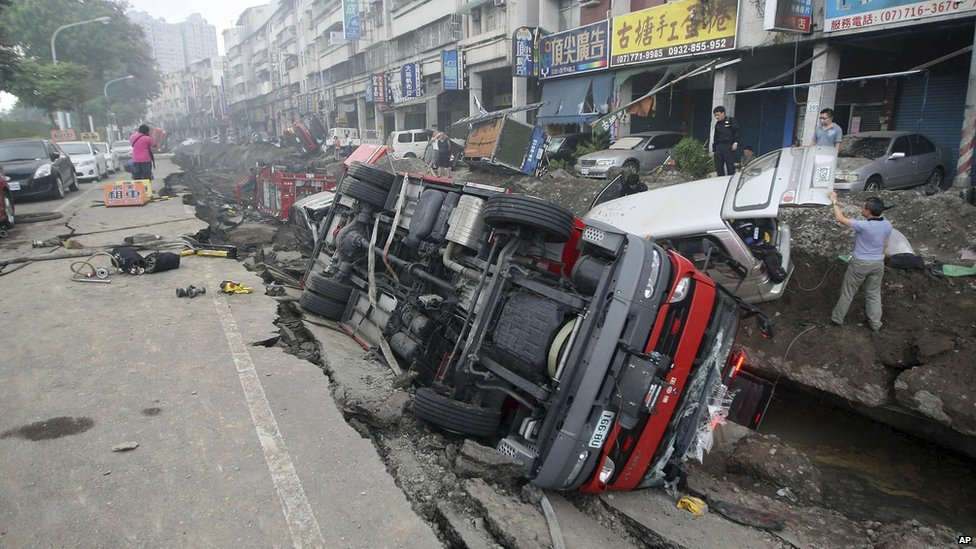 People inspect vehicles tipped over following multiple explosions from an underground gas leak in Kaohsiung, Taiwan, on 1 August 2014