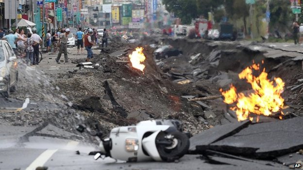 Vehicles are left lying on a destroyed street as part of the street is burning following multiple explosions from an underground gas leak in Kaohsiung, Taiwan, on 1 August 2014