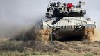 An Israeli tank advances in a staging area near the Israel-Gaza border (31 July 2014)