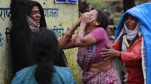 Relatives wail after seeing the body of a victim of massive landslide in the Malin village in Pune district of western Maharashtra state, India, Thursday, July 31, 2014