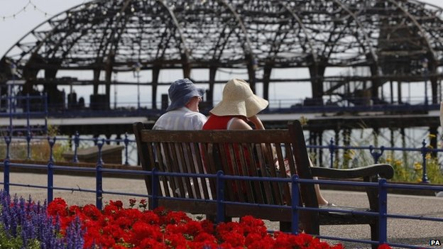 Couple on bench look at fire-damaged Eastbourne Pier