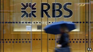 A woman walking past the headquarters of the Royal Bank of Scotland