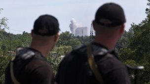 Rebel policemen watch shelling in Shakhtarsk, eastern Ukraine, 28 July