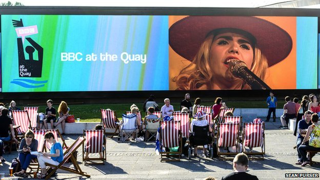 Audiences soaking up the sun in deckchairs while watching BBC at the Quay Big Screen