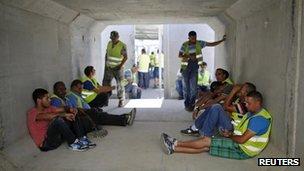 Israeli truck drivers wait inside a bomb shelter at Kerem Shalom crossing on 1 August 2014