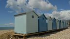 Bright blue sky with clouds dotted around. A row of blue and white beach huts, in alternating colours, lie in the foreground on the shingly beach.
