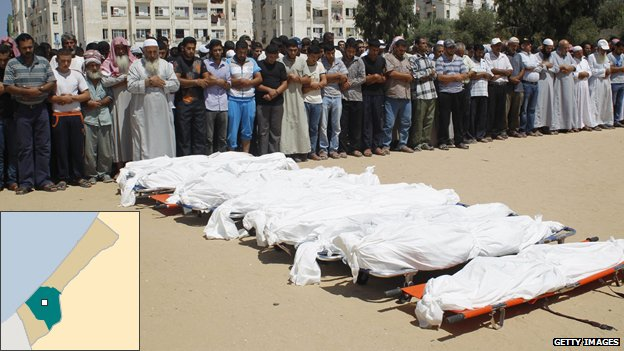 Palestinian mourners pray in front of the bodies of ten members of the al-Astal family killed in a strike on their home