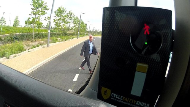 A man walks in front of a bus as part of a controlled demonstration of the Cycle Safety Shield device