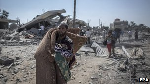 A Palestinian man walks past destroyed houses with salvaged blankets