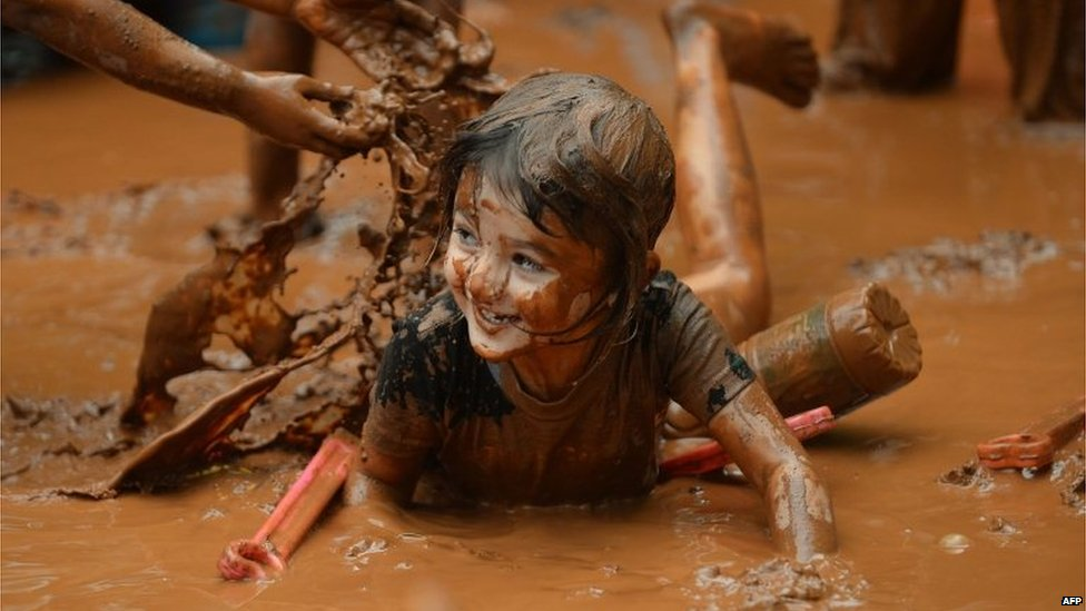 An Indian child plays in muddy water during 'Splash Puddle Day' celebrations at The Somaiya School in Mumbai.