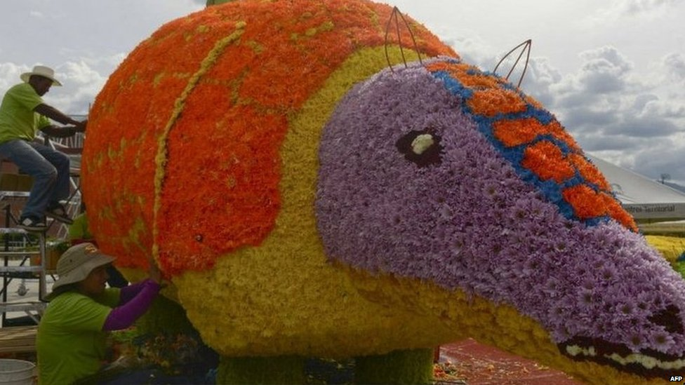 People work in a giant armadillo structure of flowers, during the Flower Festival in Medellin, Antioquia department, Colombia.