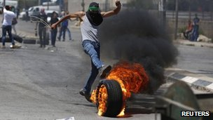 A Palestinian protester kicks a burning tyre during clashes with Israeli troops at a protest against the Israeli offensive in Gaza, outside Israel's Ofer military prison near the West Bank city of Ramallah August 1